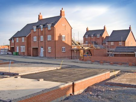 house property: New homes in the process of being built with foundations in the foreground set against a blue sky