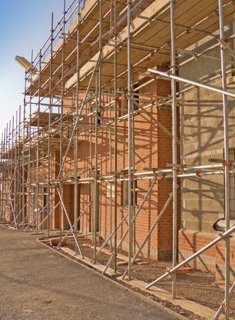 first time buyer: Line of new houses with scaffold erected being constructed