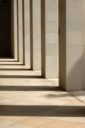 Stone columns lit from the side with long shadows cast upon the ground Stock Photo