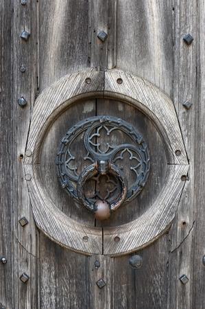 Ornate door knocker on a weathered wooden door photo