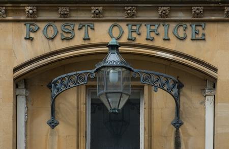 friso: Entrada a una antigua Oficina de Correos de Victoria con una linterna de hierro forjado decorado con volutas y un friso de flores por encima de la puerta