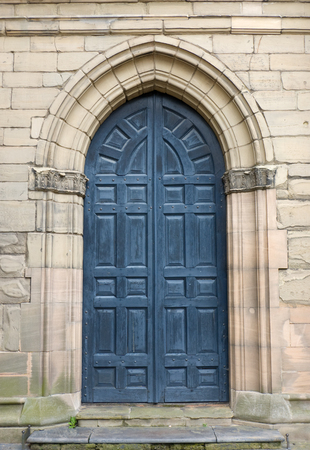 panelling: Stone semi-circular church door way and blue door with wood panelling