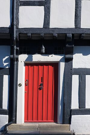 tudor: Red entrance door on a half timbered Tudor cottage Stock Photo
