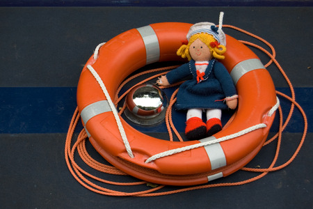 Orange lifebuoy and female rag doll with yellow hair dressed in a sailors uniform Stock Photo