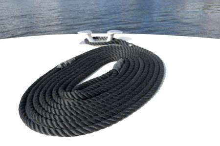 coiled rope: Black nylon mooring line or rope coiled on the deck at the bow of a boat