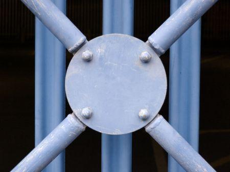 struts: Blue sheet metal boundary fence with circular disc and crisscross struts Stock Photo