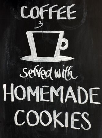 Blackboard sign with a cup motif and the words - Coffee served with homemade cookies. White on a black background