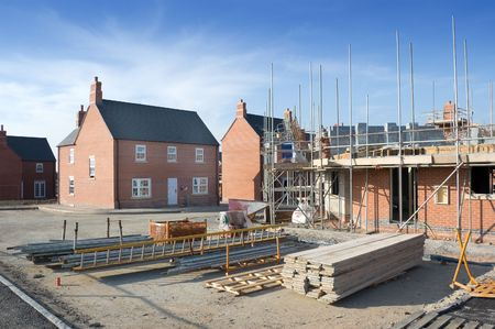 first time buyer: New homes for sale and in the foreground a new house under construction. Stock Photo