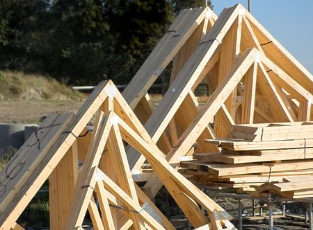 Wooden roof trusses stacked together on a building site Stock Photo