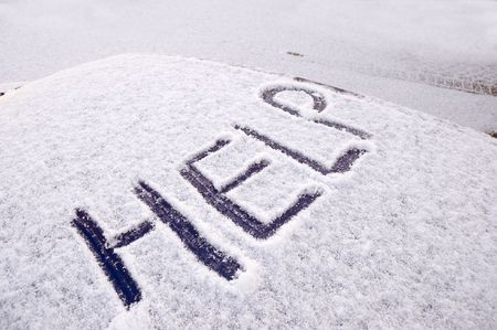 Snow covered car with the word help written on the roof Stock Photo