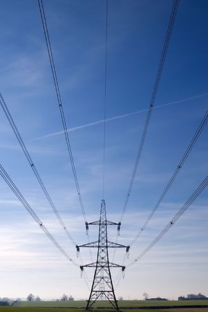 Electricity pylon and cables stretching out into the distance across a green field Stock Photo