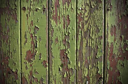 flaking: Green paint peeling from a wooden panel door showing the wood grain and old red painted surface