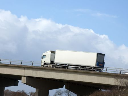 White truck with blank copy-space heading up hill on a motorway