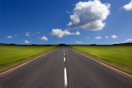road marking: Rural road stretching out into the distance with motion blur under a big expanse blue sky.  Concepts could include - road to success, new beginnings, follow your dreams etc