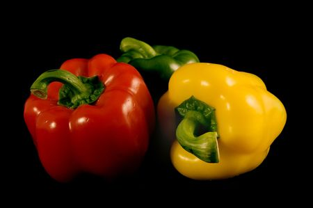 Red green and yellow Bell Peppers on a black background