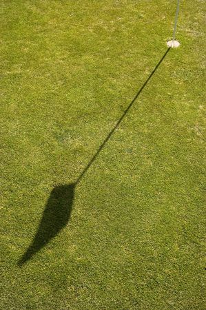 On the Putting green of a golf course the flag and pin or stick casting a shadow on the green
