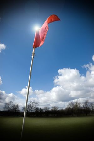 Red golf flag fluttering in the wind lit by the sun Stock Photo - 2814219