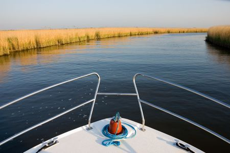 Bow of a white boat cruising along a calm blue river past golden yellow reedbeds looking towards the distant horizon
