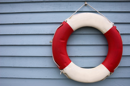 Red and White Lifebuoy hanging on a blue painted wooden fence panel.