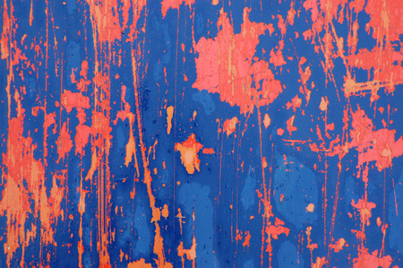 Background texture of orange and blue paint peeling off a metal plate