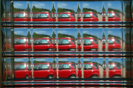 Abstract view of a red car seen repeated through a glass brick.