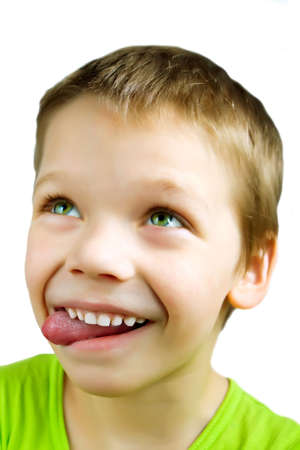 Young boy with eyes rolled up and tongue out making a very funny face on white background Stock Photo