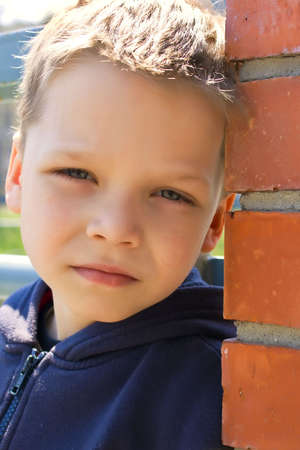 about you: Quiet boy about a brick wall in an summer park looks on you