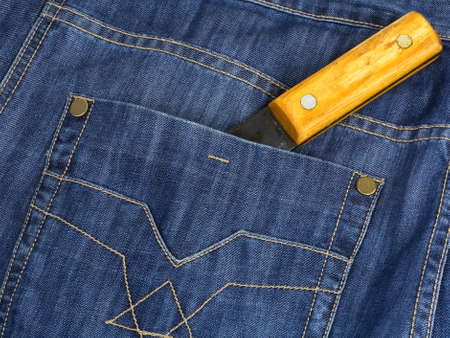 latent: The hatchet handle is shown from a pocket jeans. The concept of the latent danger. Stock Photo