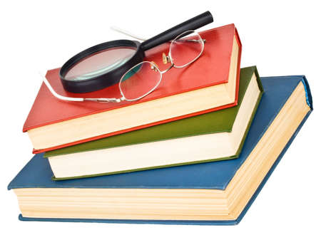 Glasses and magnifying glass on a pile of books, isolated on white background photo