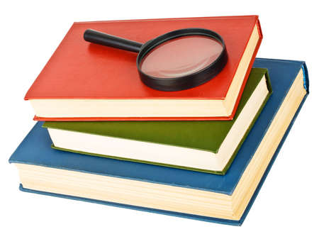 Magnifying glass on a pile of books, isolated on white background photo