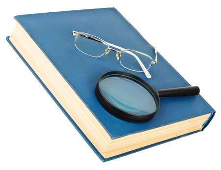 Glasses and magnifying glass on a blue book, isolated on white background photo