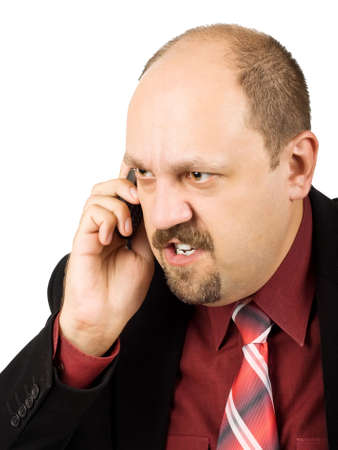 spiteful: Spiteful businessman with crazy eyes talking by mobile phone, and receiving bad news, isolated on white background Stock Photo