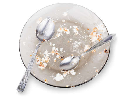 Empty dirty plate with spoons isolated on the white background