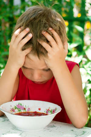 little table: A little boy holding his hands behind his head and looks at his food - soup Stock Photo