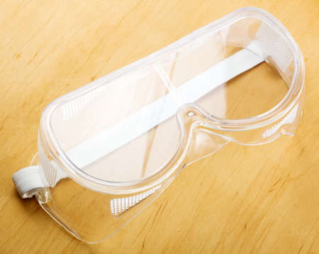 medical personal: Industrial safety glasses - over a wooden background Stock Photo