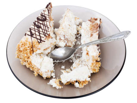Slice of cake on a glass plate, with spoon and on white background photo