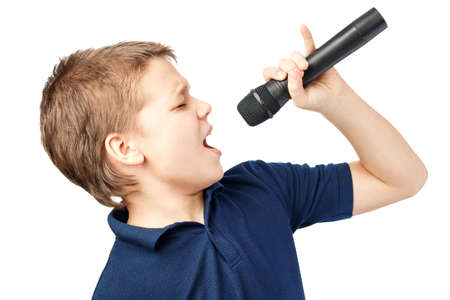 Boy singing into a microphone. Very emotional. Foto de archivo