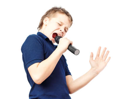 cute teen: Boy singing into a microphone. Very emotional. Stock Photo