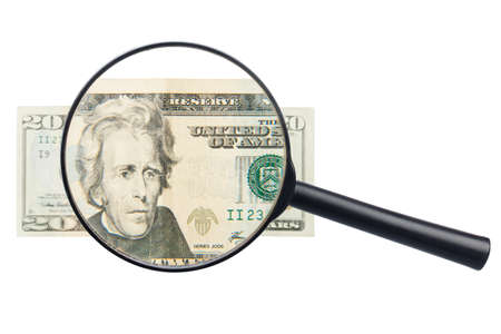 counterfeiting: Twenty dollars bill and magnifying glass isolated on white