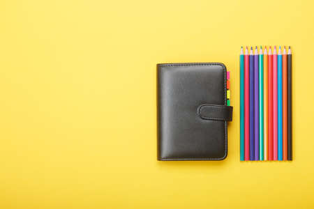 Notebook and color pencils on a yellow background. Mock up with copy space for your ideas. Flat lay style. Stock Photo