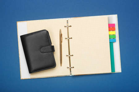 Notebook and pen on a blue background. Flat lay style.