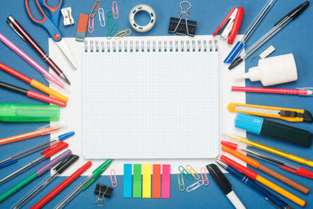 Stationery and blank notebook on blue background. Education concept with copy space for your ideas. Flat lay style.