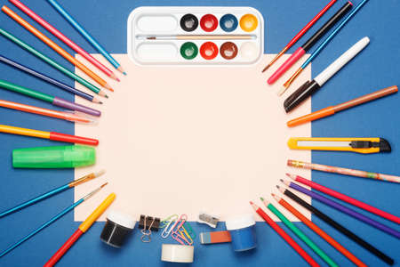Stationery and blank paper on blue background. Education concept with copy space for your ideas. Flat lay style.