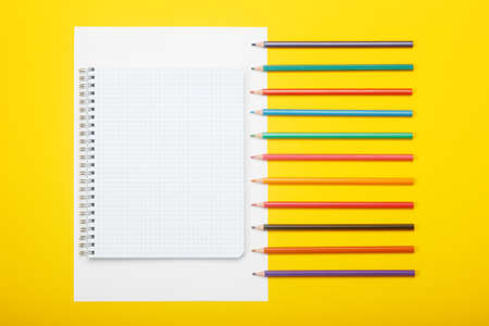 Notebook and color pencils on a yellow background. Mock up with copy space for your ideas. Flat lay style. Reklamní fotografie