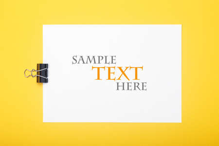 Blank paper with clamp on yellow background. Mockup with sample text for your design. Flat lay style. Reklamní fotografie