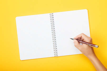 Hand with pen over blank notebook on a yellow background. Mock up with copy space for your ideas. Flat lay style. Reklamní fotografie