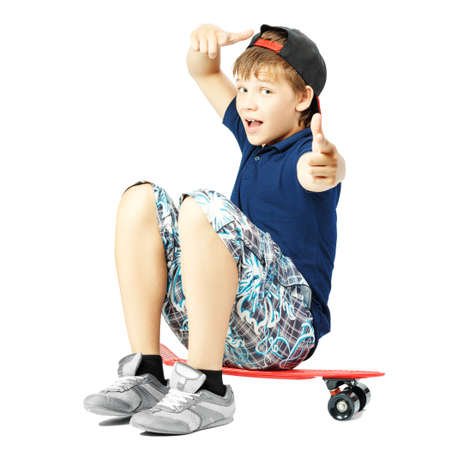 Teenager with funny expression face gesticulates with a hands, sitting on a skateboard isolated on white background