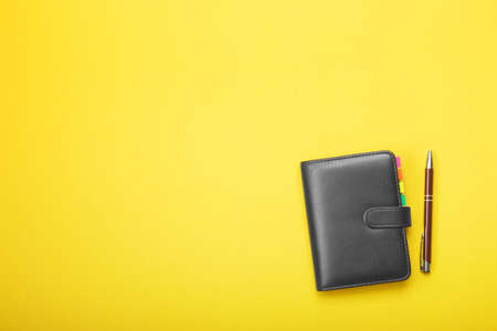 Notebook and pen on a yellow background. Flat lay style. Reklamní fotografie
