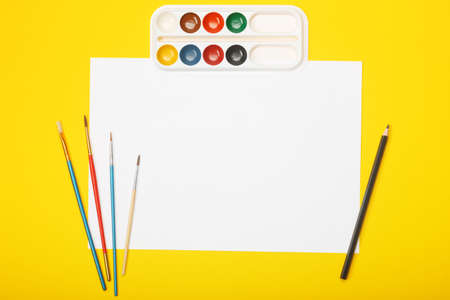 Blank paper with pencil, brushes and paints on yellow background. Artist workplace concept with copy space for your ideas. Flat lay, top view. Zdjęcie Seryjne