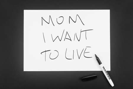 Written in black marker on a white piece of paper: Mom, I want to live. The concept of severe illness in the last stage, despair, hopelessness, death. The child writes to his mother.